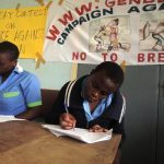 Girls writing their essays on violence against women in Cameroon.
