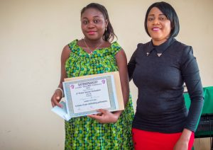 Mme Basang Victory from the Regional Delegation of Ministry of Communication hands over prize to one of the winners